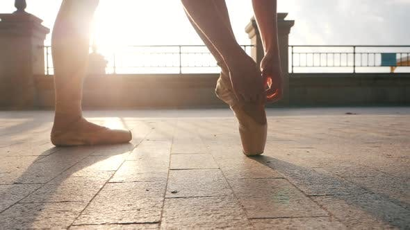 Thumbnail for Close Up of a Ballet Dancer's Feet As She Corrects Pointe on the Stone Embankment. Woman's Feet in