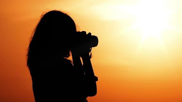Thumbnail for Female Photographer at Sunrise Warm Sky with Orange Sun
