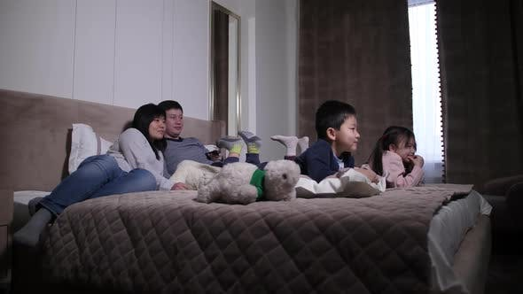Thumbnail for Happy Asian Family with Kids Watching TV on Bed
