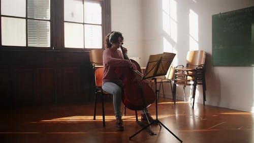 Cellist Rehearsing In Classroom