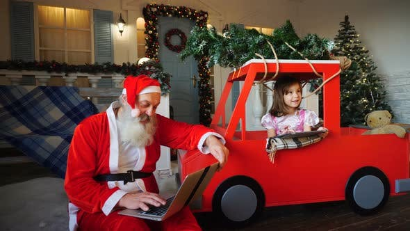 Thumbnail for Joyous Santa Claus Satisfying with Laptop and Little Girl Playing on Tablet.
