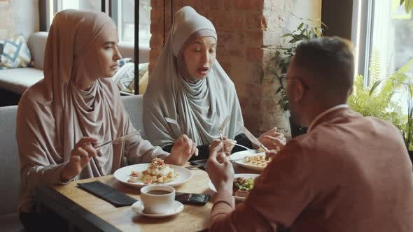 Thumbnail for Muslim Women Having Lunch and Talking with Male Friend in Cafe