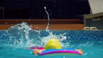 A Cute Little Child in Swimming Caps Performs an Assignment in a Swimming Lesson in the Pool