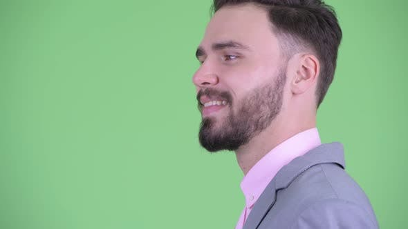 Thumbnail for Closeup Profile View of Happy Young Bearded Businessman Smiling