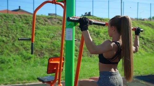 Sportswoman Training Back Muscles Using Simulator Outdoors