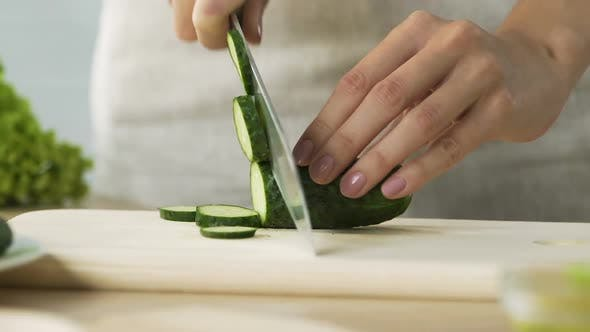 Thumbnail for Woman chopping fresh cucumber cooking healthy salad for family dinner, close-up