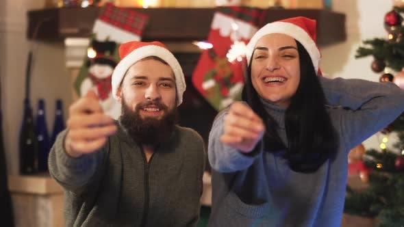 Thumbnail for Mann und Frau sitzen in der Nähe von Weihnachtsbaum, Frau hält Funkeln in der Hand und küssen. Wunderkerze