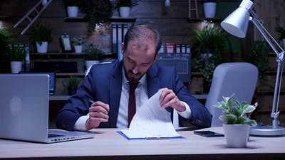 Businessman Signs Contracts Late at Night in the Office