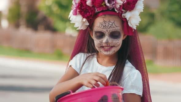 Mädchen Überprüfung ihr Halloween-Korb nach Trick-oder-Behandlung