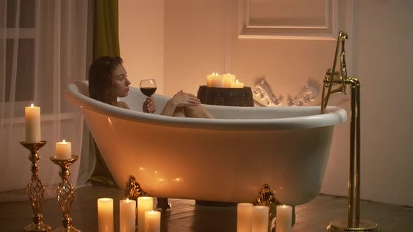 Thumbnail for Woman Lying in Bubble Bath with the Light From the Candles To Relax and Drink Wine