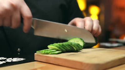 Slicing of a Cucumber in the Restaurant Kitchen