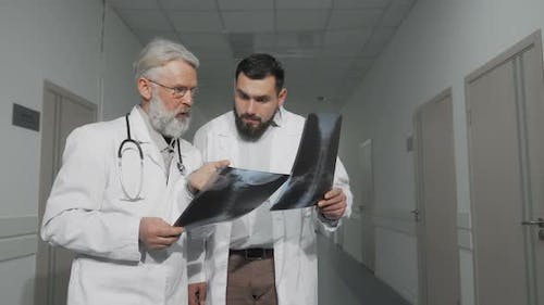Two Doctors Talking in Hospital Hallway Examining X-ray Scans Together