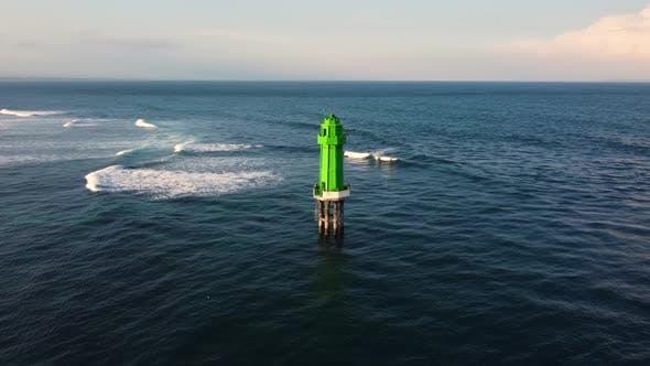 Green Lighthouse in the Ocean on Sunset