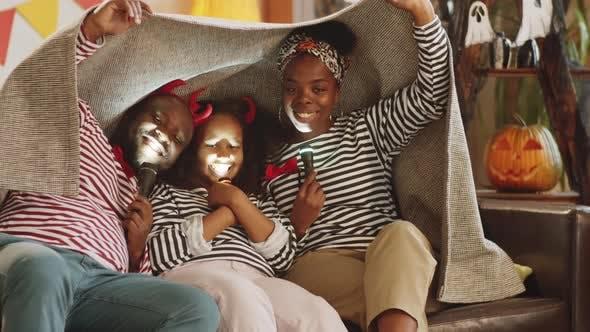 Thumbnail for Fröhliche Familie posiert mit Taschenlampen unter Decke auf Halloween