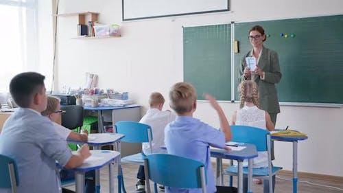 Grundschulpädagoge zeigt Pupillenkarten mit Buchstaben Smart Kids hebt Hände, weiß richtig