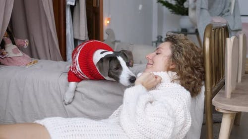 Young Woman Plays with Dog Waiting for Guests to Arrive for New Year Home Dinner Party