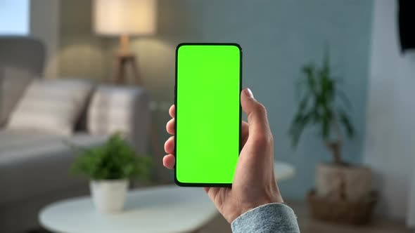 Thumbnail for Close-up Shot of Young Man at Home Sitting on a Chair Using With Green Mock-up Screen Smartphone