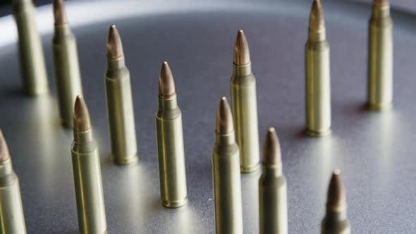 Cinematic rotating shot of bullets on a metallic surface