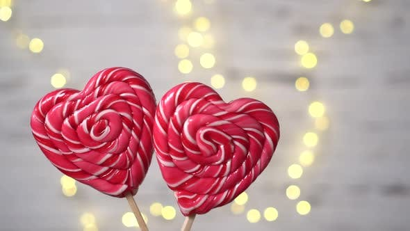 Two Heartshaped Candies Move Against the Background of Lights