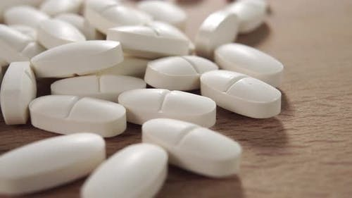 White oval tablets on a wooden surface close-up. Healing pills