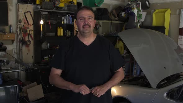 Thumbnail for Static shot of a handyman in a dimly lit garage.