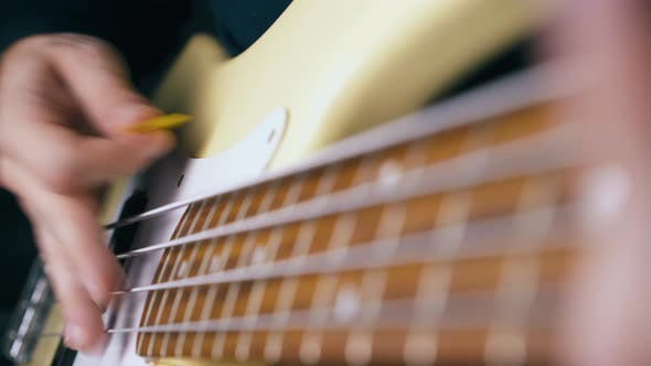 Thumbnail for Person Plays Bass Guitar with Yellow Pick and Sets Pace