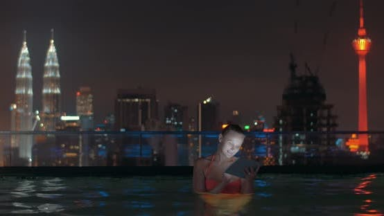 Cover Image for Woman with Pad in Rooftop Pool of Night Kuala Lumpur