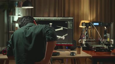 Back View Of Asian Engineer Paining His Back While Work On Personal Computer And 3D Printer