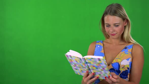 Thumbnail for Young Pretty Blond Woman Reads Book - Green Screen - Studio