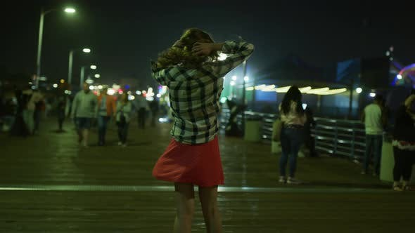 Thumbnail for Young woman spinning on Santa Monica Pier, at night
