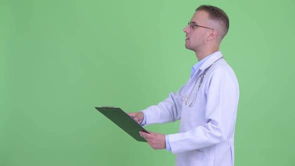 Thumbnail for Profile View of Happy Handsome Man Doctor Reading on Clipboard