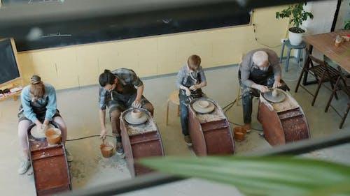Creative People Potters Making Ceramics Using Throwing Wheels in Workshop