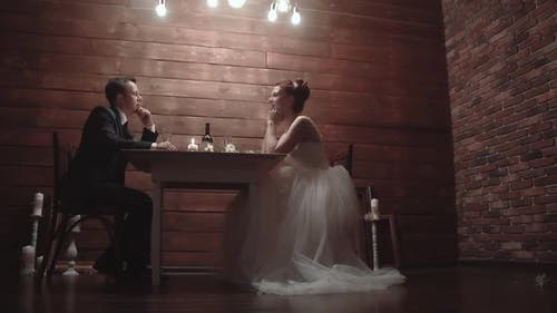 Young Couple in a Wedding Attire, Sitting in a Restaurant and Talking, During Dinner. Slow Motion