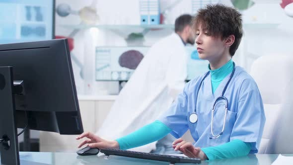 Thumbnail for Young Nurse Typing on Computer Keyboard