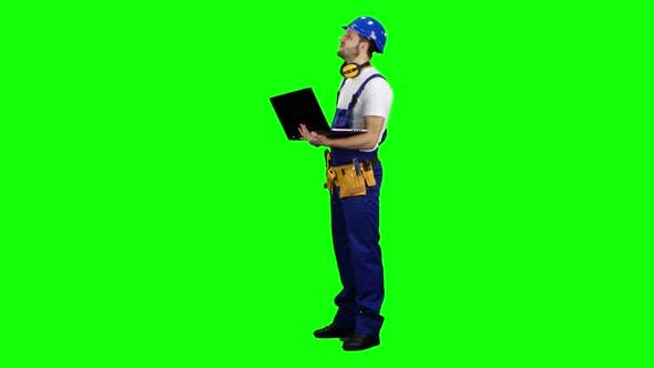 Thumbnail for Foreman mit einem Laptop sagt, wie man ein Gebäude baut. Grüner Bildschirm