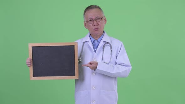 Thumbnail for Stressed Mature Japanese Man Doctor Holding Blackboard and Giving Thumbs Down