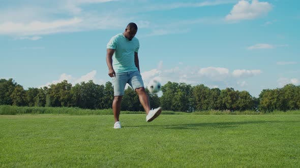 Thumbnail for African Man Bouncing Soccer Ball on Leg Outdoors