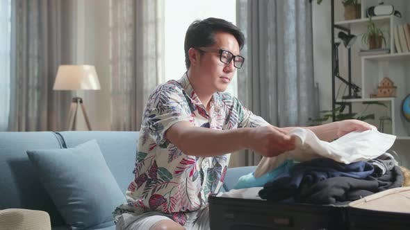 Asian Young Man Packing Clothes In Suitcase At Home, Preparing For Vacation