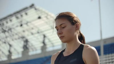 Beautiful Woman Athlete at the Stadium Breathing and Preparing To Start the Race. Motivation and