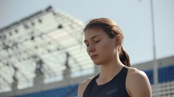 Thumbnail for Beautiful Woman Athlete at the Stadium Breathing and Preparing To Start the Race. Motivation and