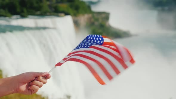 Cover Image for Hand with USA Flag on Niagara Falls Background