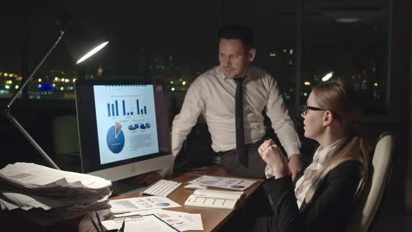 Thumbnail for Business People Analyzing Statistics at Night