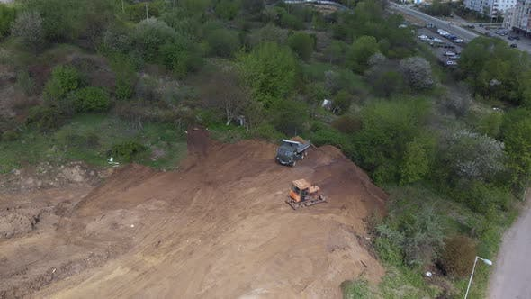 Aerial shot of tipper unloading ground on further construction site.