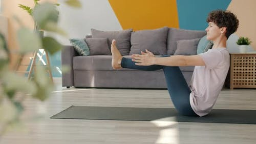 Cute Young Woman Doing Yoga Balancing in Seated Position Developing Stamina