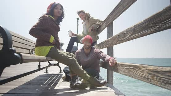 Thumbnail for Relaxed hip urban friends hanging out on pier during spring break
