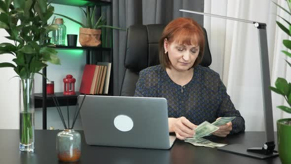 Middle-aged businesswoman is counting money sitting in her modern office