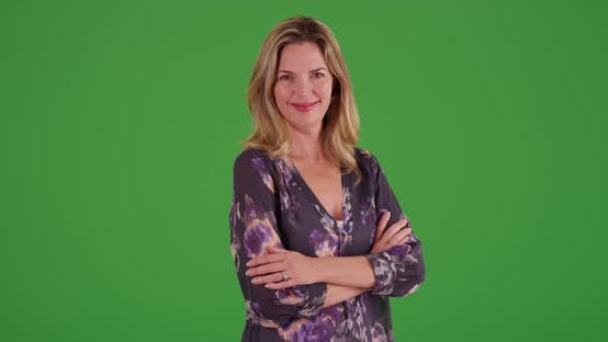 Thumbnail for Caucasian woman with arms crossed, smiling at camera on green screen