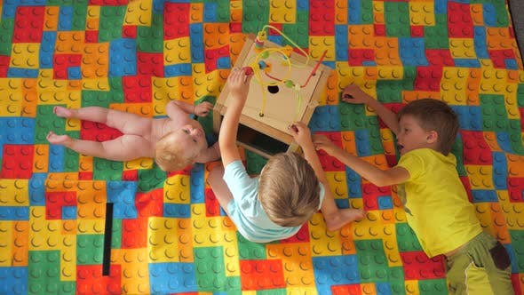Thumbnail for Three children playing with a Montessori toy. Games for brain development. Preschool of life.