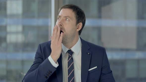 Thumbnail for Sleepy Businessman Yawning While Sitting at Work