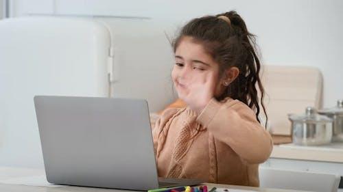 Kleines Arabisches Mädchen winkt Hallo zum Laptop in der modernen Küche